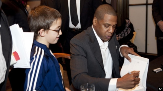Entrepreneur and rapper Jay-Z signs a copy of his book, 'Decoded,' for a young fan at the New York Public Library.