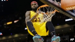 Cleveland Cavaliers forward LeBron James (23) hangs onto the basket after a dunk during the second half of an NBA basketball game against the Miami Heat in Miami, Dec. 25, 2014. James was called for a technical foul on the play.