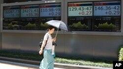 一名妇女走过东京一家证券公司的电子屏幕
