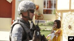 A US soldier attached to the Golden Lions forces walks past a girl carrying her doll, during a patrol in the city of Kirkuk, July 20, 2011