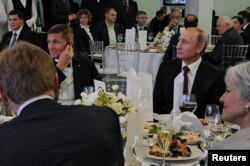 FILE - Russian President Vladimir Putin (R) sits next to retired U.S. Army Lieutenant General Michael Flynn (L) as they attend a banquet marking the 10th anniversary of RT (formerly Russia Today) television news channel in Moscow, Russia, Dec. 10, 2015.