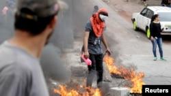 洪都拉斯抗议者点燃一个街障抗议总统胡安·奥兰多·埃尔南德斯连任。(2018年1月20日)