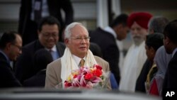 FILE - Malaysian Prime Minister Najib Razak holds a bouquet of flowers presented to him upon arrival in New Delhi, India, March 31, 2017.