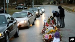 Protesters gather near a memorial in the middle of the street, Nov. 24, 2014, more than three months after a black 18-year-old man was shot and killed there by a white policeman in Ferguson, Mo.