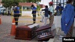 Orang-orang menunggu di sebelah peti mati di luar Rumah Sakit Umum Guasmo Sur setelah Ekuador melaporkan kasus corona di Guayaquil, Ekuador 1 April 2020. (Foto: Reuters/Vicente Gaibor del Pino)