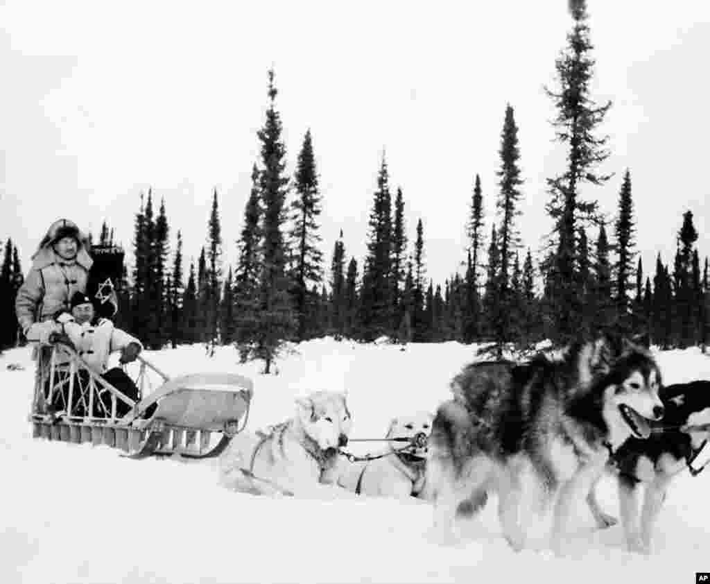 1945: Jewish Chaplain Harold Gordon and Catholic Chaplain William Woods use dog sleds when they can't get to the men by the planes of the Army Transport Command for Passover and Easter services. (Photo courtesy Jewish Chaplains Council)