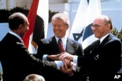 In this March 26, 1979, file photo, Egyptian President Anwar Sadat, left, U.S. President Jimmy Carter, center, and Israeli Prime Minister Menachem Begin clasp hands on the North lawn of the White House as they completed signing of the peace treaty