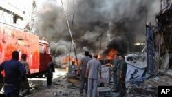 Quelques personnes se rassemblent autour des bâtiments en feu après une attaque à la bombe dans la banlieue de Sayyida Zeinab, à Damas, Syrie, 11 juin, 2016.