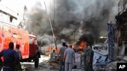 Quelques personnes se rassemblent autour des bâtiments en feu après une attaque à la bombe dans la banlieue de Sayyida Zeinab, à Damas, Syrie, 11 juin, 2016. (SANA via AP)