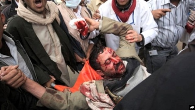 A wounded Yemeni anti-government protester is carried away by fellow demonstrators in Sana'a March 18, 2011