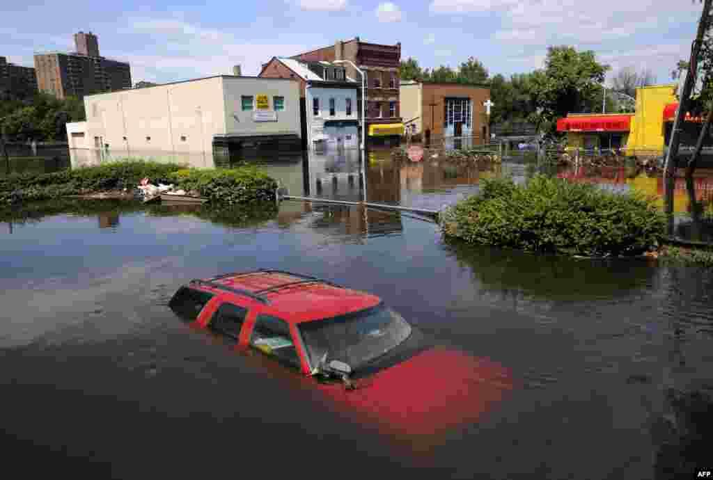 30 tháng 8: Nước phủ khắp đường phố và nhận chìm một chiếc xe ở thành phố Paterson, bang New Jersey Hoa Kỳ sau bão Irene. REUTERS/Mark Dye