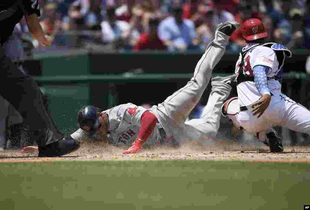 កីឡាករRafael Devers (ឆ្វេង) កំពុងរំអិលខ្លូនទៅលើស្មៅ ដោយឆ្លងកាត់មុខកីឡាករPedro Severino នៃក្រុមWashington Nationals ដើម្បីយកពិន្ទុ ក្នុងការប្រួតបាល់ Baseball នៅរដ្ឋធានីវ៉ាស៊ីនតោន។