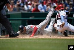 Boston Red Sox' Rafael Devers, left, slides home past Washington Nationals catcher Pedro Severino to score on a sacrifice fly by Jackie Bradley Jr., during the seventh inning of a baseball game Wednesday, July 4, 2018, in Washington.