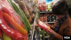 河内一个食品商店里陈列的蔬菜。一名购物者在挑选蔬菜。