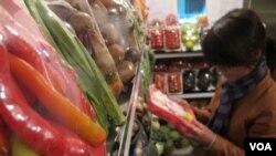 Khách hàng đọc thông tin trên bao bì đóng gói rau quả tại siêu thị veggie ở Hà Nội