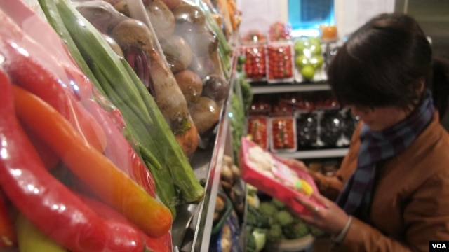 "A shopper reads packaging on vegetables on sale at Veggies, a grocery shop in central Hanoi listed on a website providing consumers with information on where to buy ""safe"" vegetables, March 28, 2014. (Marianne Brown/VOA)"