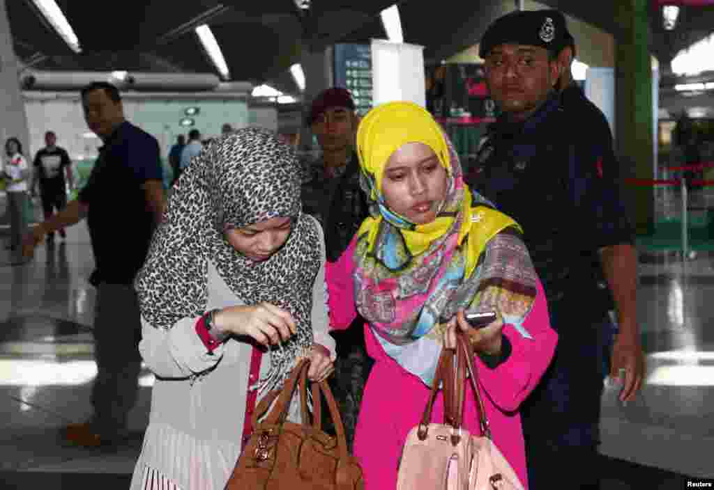 Family members of those onboard the missing Malaysia Airlines flight walk into the waiting area at Kuala Lumpur International Airport in Sepang.