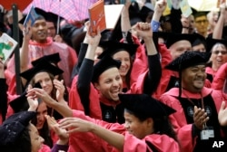 FILE – Students celebrate after graduating from the Harvard School of Education during Harvard University commencement exercises in Cambridge, Mass., May 25, 2017.