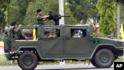 A military vehicle with a mounted grenade launcher makes its way during clashes between Thai and Cambodia in Surin province, northeastern Thailand, Thursday, April 28, 2011. Thai and Cambodian military commanders agreed to a cease-fire Thursday after sev