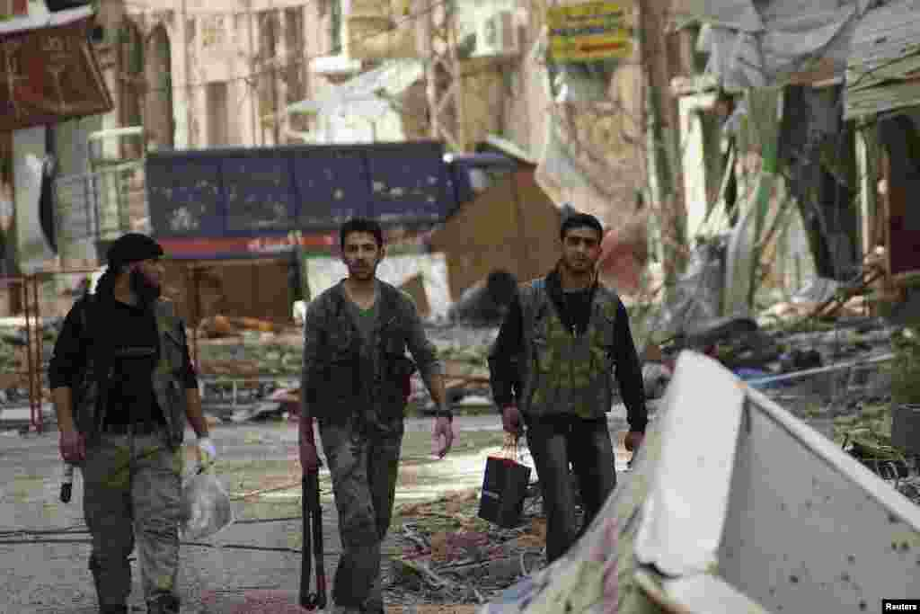 Syrian fighters walk along a street of damaged shops and buildings in Deir al-Zor, April 8, 2013.