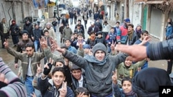 Anti-Syrian regime protesters chant slogans and flash the victory sign as they march during a demonstration at the mountain resort town near the Lebanese border, Zabadani, Syria, January 17, 2012.