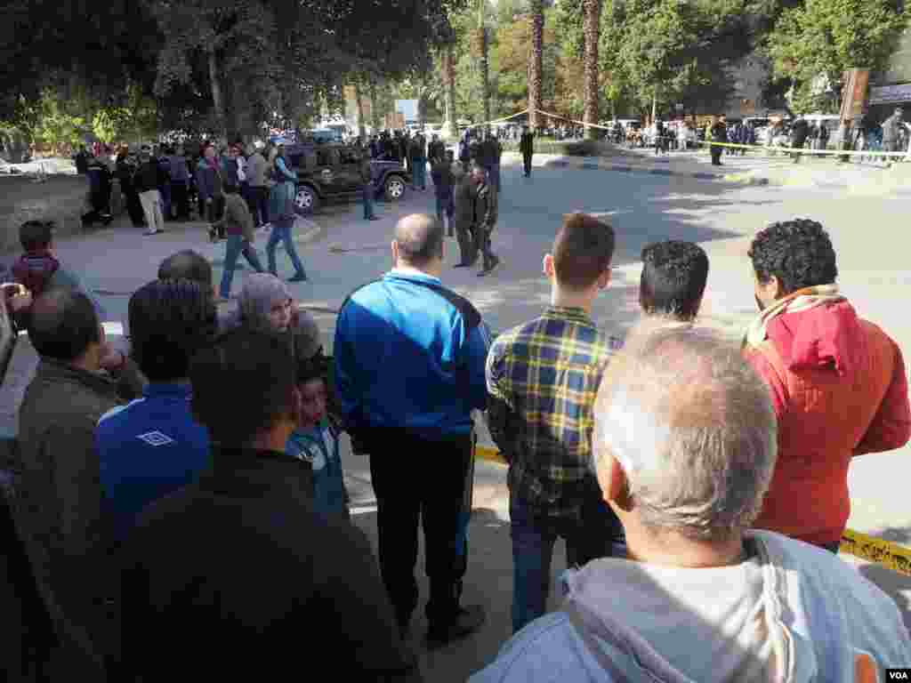 Residents watch the inspection of the explosion in Giza, Egypt, Dec. 9, 2016. The explosion hit at 9:30 a.m., and then police blocked the road. (H. Elrasam/VOA)