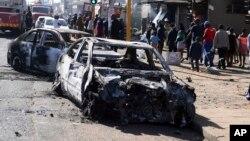 2019年9月2日行人在约翰内斯堡郊区街道旁经过暴力事件中烧毁的汽车。