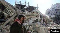 12일 정부군과 반군 간 교전으로 무너진 다마스쿠스 건물 앞을 지나는 반군 병사.