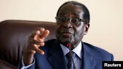 Zimbabwe's President Robert Mugabe gestures while addressing a meeting of his ZANU-PF party's supreme decision making body in Harare, August 7, 2013.