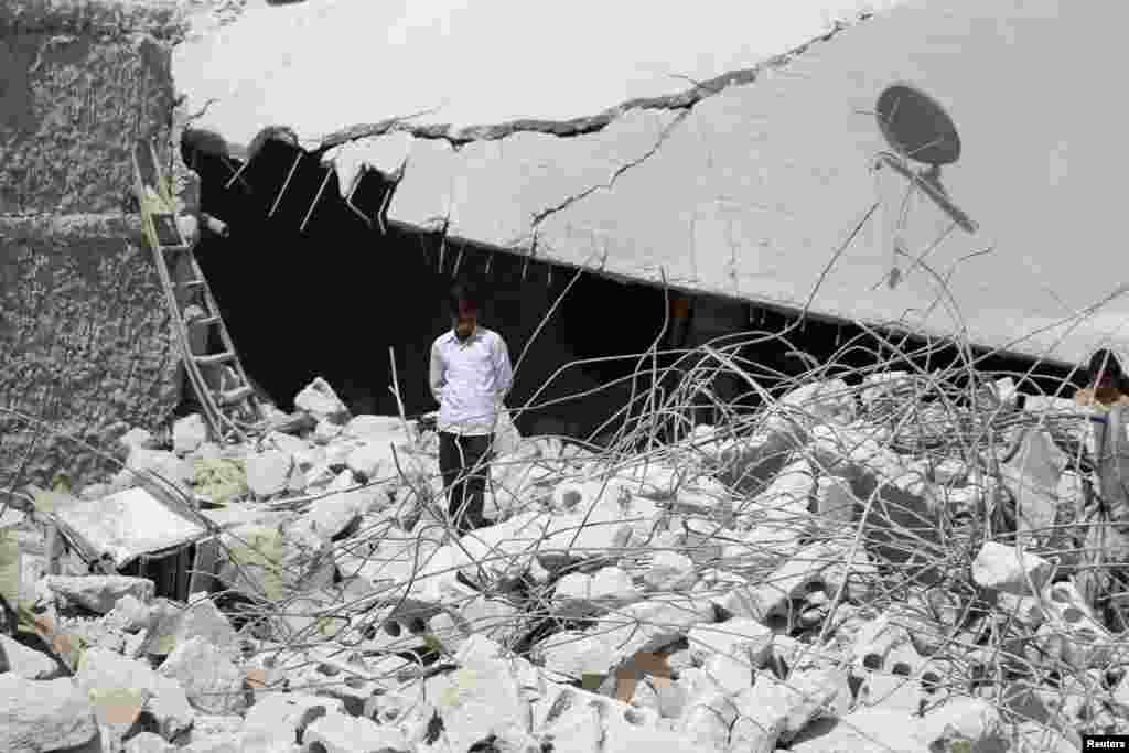 A resident walks upon the debris of buildings which were damaged in what activists say was one of the U.S. air strikes in Kfredrian, Idlib province, Iraq.