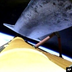 The space shuttle Atlantis releases its fuel tank for the final time, July 8, 2011