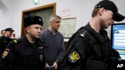 Founder of the Baring Vostok investment fund Michael Calvey, center, is escorted to the courtroom in Moscow, Feb. 15, 2019. A veteran U.S. investment fund manager has been detained in Moscow and faces fraud charges.