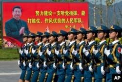 2015年8月22日,中国女兵在练习中走过标语牌
