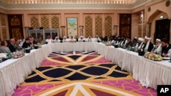 FILE - This photo released by Qatar's Ministry of Foreign Affairs shows Qatari, U.S. and Taliban officials conferring in an undisclosed place in Doha, Feb. 25, 2019, ahead of the latest round of talks with the insurgents aimed at ending the Afghan war.