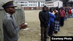 Voters waiting to vote outside a polling station in Harare