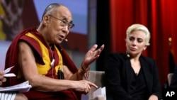 Lady Gaga (kanan) mendengarkan Dalai Lama berbicara pada sesi tanya jawab pada Konferensi Walikota Amerika di Indianapolis, Minggu (26/6).