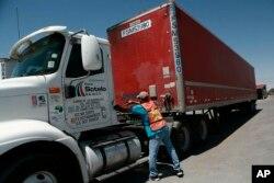 """ພະນັກງານຄົນນຶ່ງ ພວມຕື່ມນ້ຳມັນລົດບັນທຸກ ທີ່ເຕັມດ້ວຍສິນຄ້າຂາເຂົ້າ ທີ່ບໍລິສັດຂົນສົ່ງ """"Fletes Sotelo"""" ໃນເມືອງ Ciudad Juarez ປະເທດເມັກຊິໂກ ເມື່ອວັນທີ 7 ມິຖຸນາ ປີ 2019."""