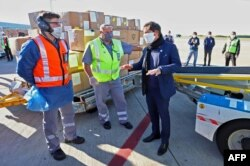 Handout picture released by the Buenos Aires province Ministry of Public Communication showing Buenos Aires province Governor Axel Kicillof (R) speaking with workers while the unloading of boxes containing medical supplies coming from China.