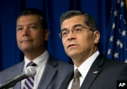 FILE - California Attorney General Xavier Becerra, right, flanked by Secretary of State Alex Padilla, speaks to reporters at the Capitol in Sacramento, Sept. 5, 2017.