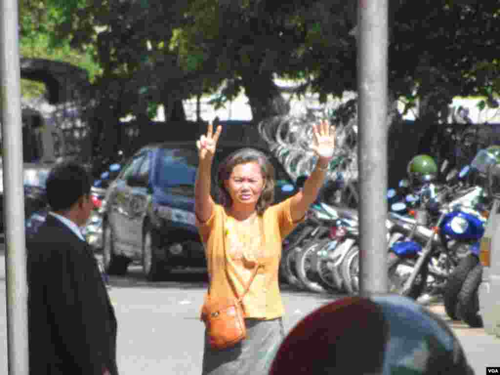 Mu Sochua raises her hands showing a seven-finger sign, representing her party, to supporters from inside a police compound, Phnom Penh, Cambodia, July 15, 2014. (Khoun Theara/VOA)
