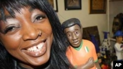 Osso Reine holds one of the wooden figurines sold in her shop...this one's in the image of an Ivorian soccer player