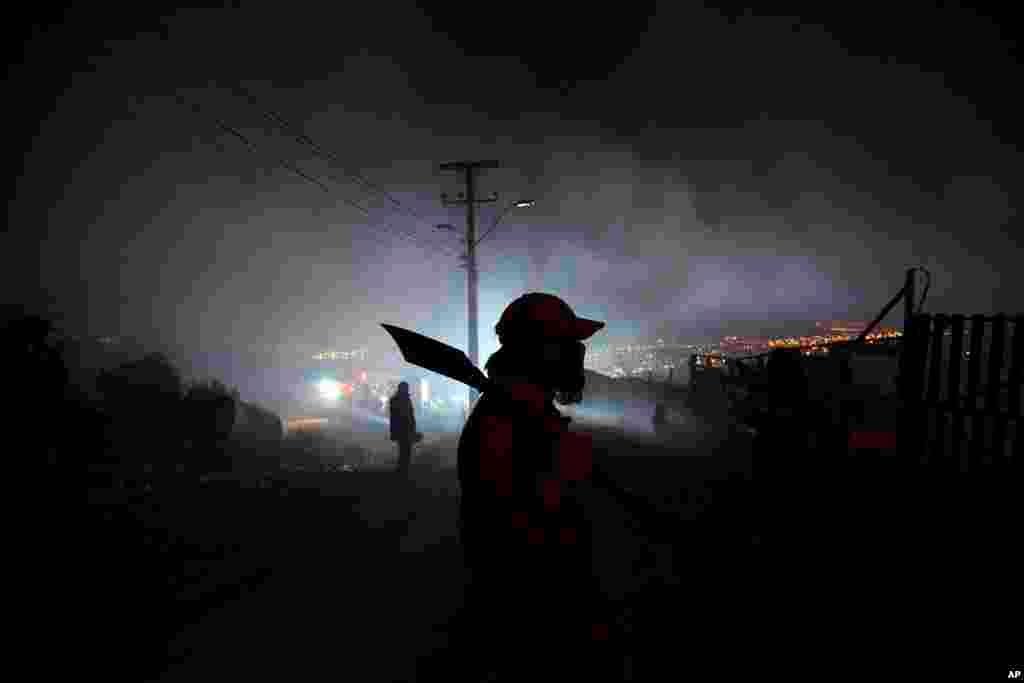 Um morador ajuda a apagar as chamas enquanto o fogo fora de controle vai destruindo as casas na cidade de Valparaiso, Chile, Abril 13, 2014.
