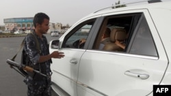 FILE - A Yemeni soldier inspects a vehicle at a checkpoint in the Yemeni capital of Sanaa on July 16, 2014.