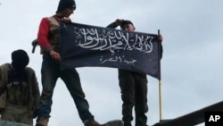 FILE - Rebels from al-Qaida-affiliated Jabhat al-Nusra wave their brigade flag as they stand atop a Syrian air force helicopter at Taftanaz air base, Jan. 11, 2013.