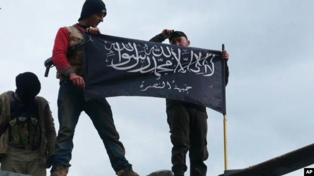 FILE - Rebels from al-Qaida-affiliated Jabhat al Nusra, also known as the Nusra Front, wave their brigade flag, as they step on the top of a Syrian air force helicopter at Taftanaz air base, Jan. 11, 2013.