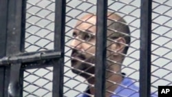 FILE - Saif al-Islam Gadhafi, son of Libya's former stongman Moammar Gadhafi, is shown inside a courtroom cage, Zintan, Sept. 19, 2013.