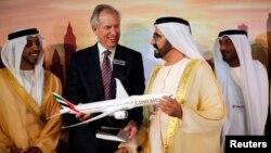 Глава компании Boeing Джеймс Макнирни (второй слева) показывает премьеру ОАЭ шейху Мохаммеду бин Рашиду аль Мактуму (второй справа) модель новой модификации дальнемагистрального лайнера «Boeing 777X». Дубай 17 ноября 2013 г.
