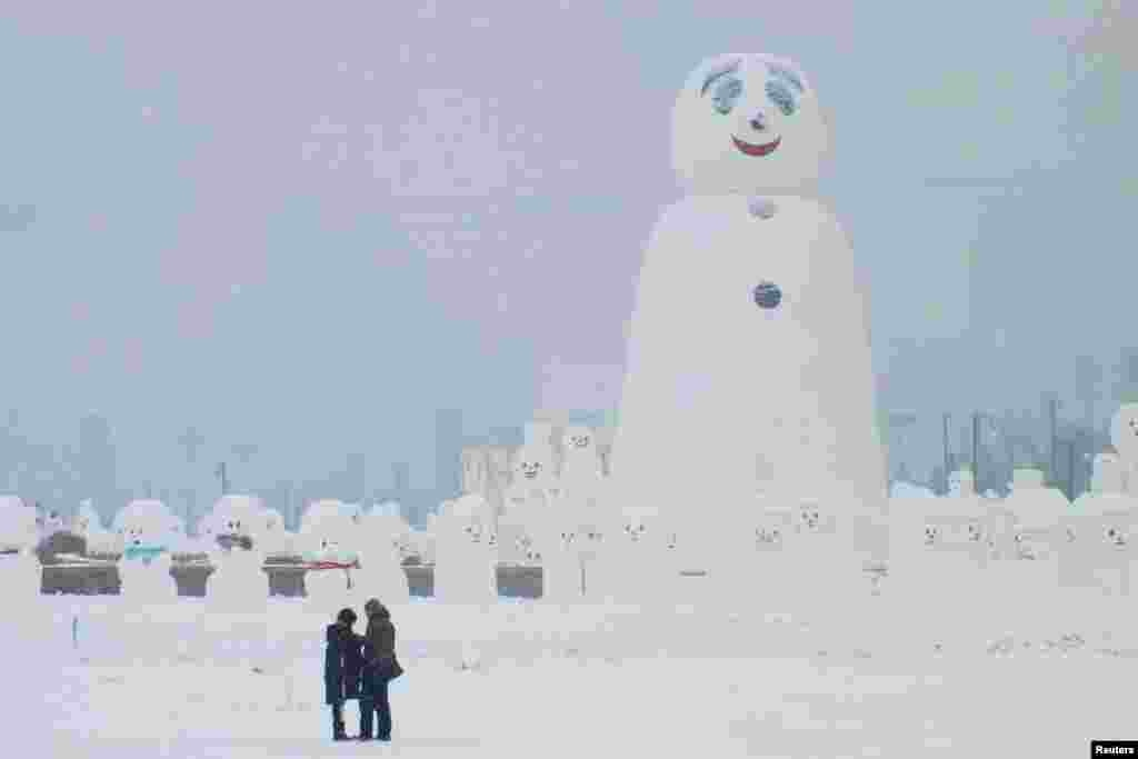 中国哈尔滨的国际冰雪雕塑节期间,大小雪人雪狗列队,一览游客小(2018年1月8日)