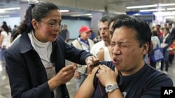 A man is vaccinated against swine flu by a nurse in a subway station in Mexico City. (Jan. 18, 2010)