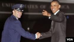 Presiden Barack Obama (kanan) mendengarkan kru media menyanyikan lagu 'Happy Birthday' sesaat setelah ia mendarat di Lapangan Udara Andrews (04/8).